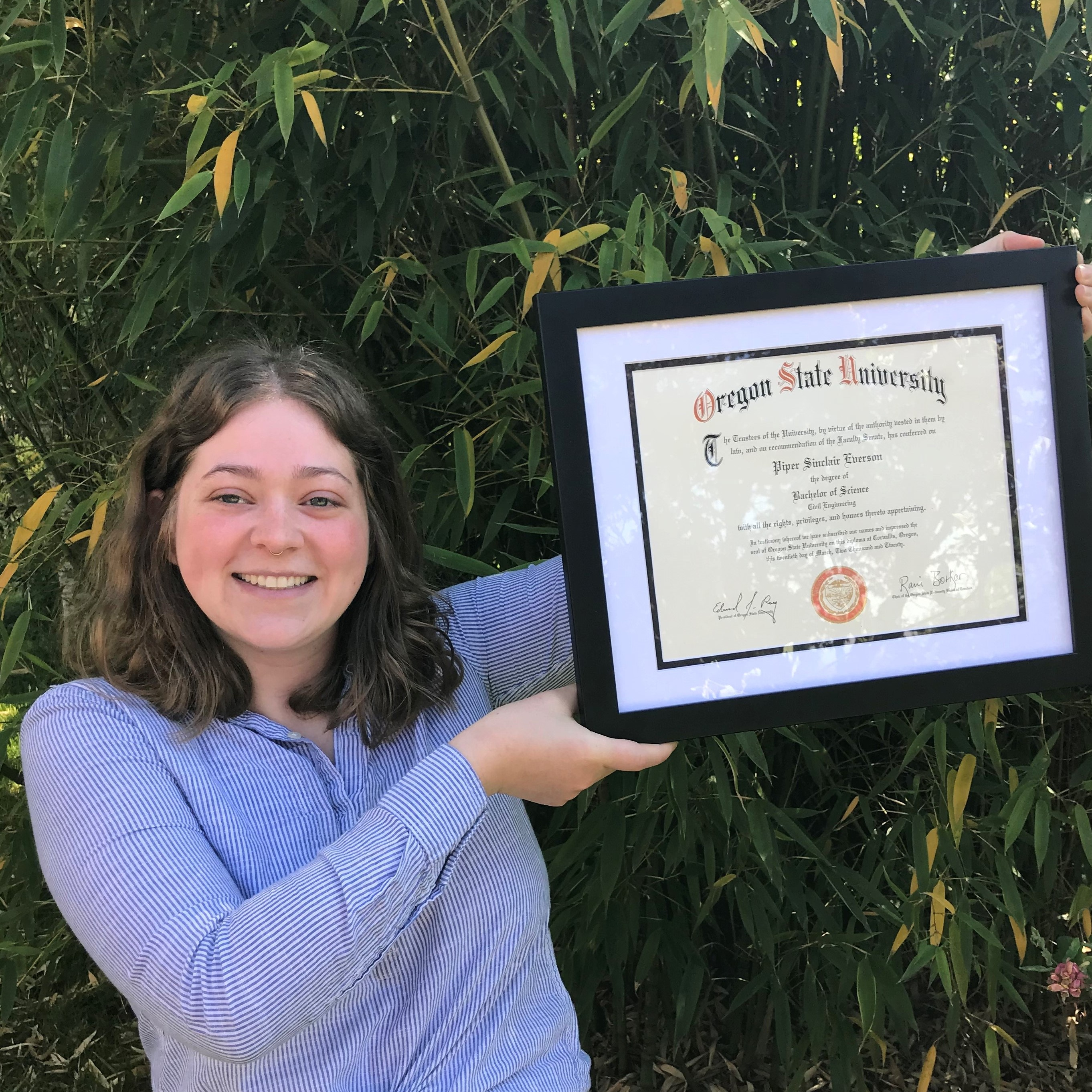 Piper Everson holding diploma