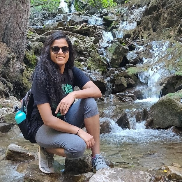 Sneha Raza poses in front of a waterfall