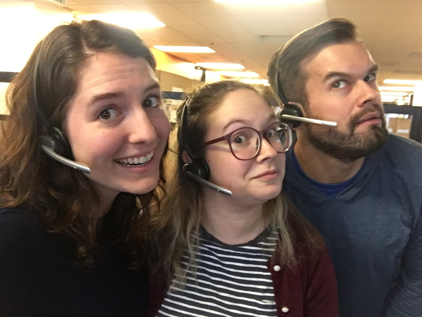 Clara Olson with co-workers wearing headsets and smiling